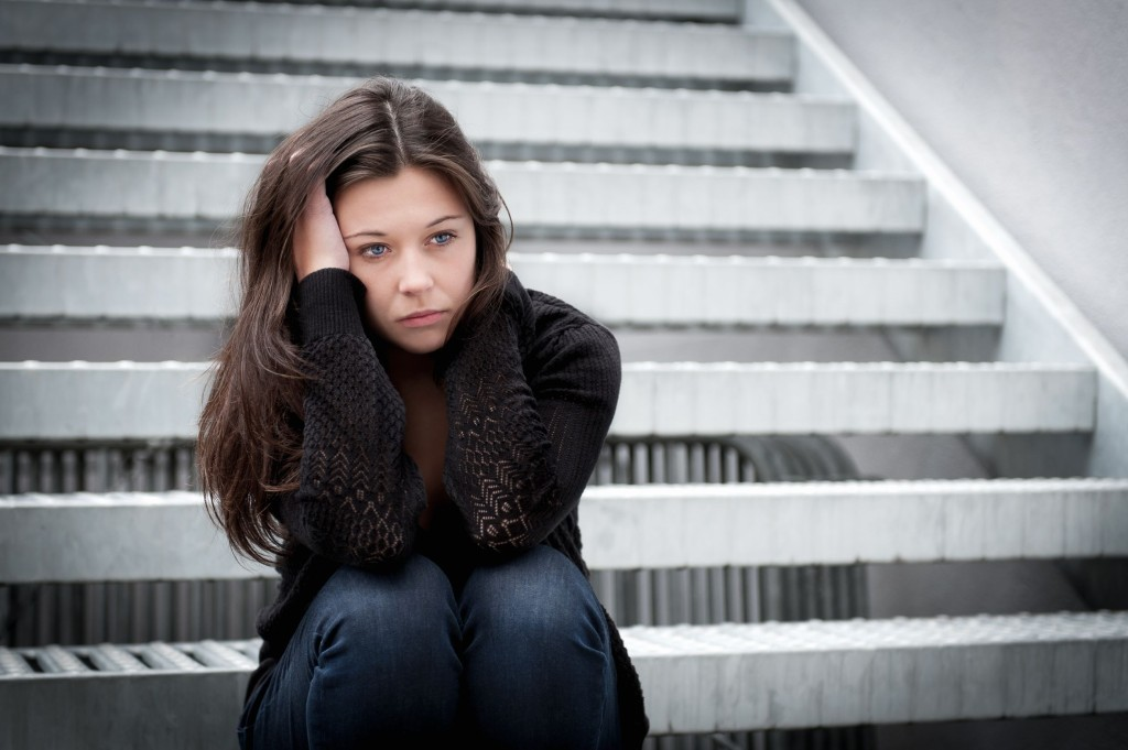 14247671 - outdoor portrait of a sad teenage girl looking thoughtful about troubles in front of a gray wall